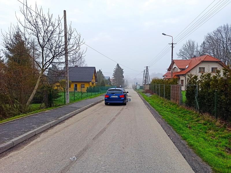 Droga łącząca Biery i Świętoszówkę. Drogą porusza się niebieski samochód.